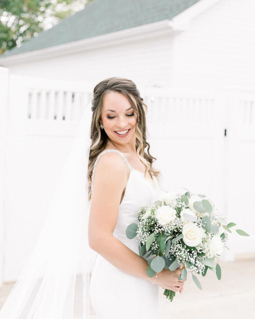 bride in long veil holding white and green bouquet