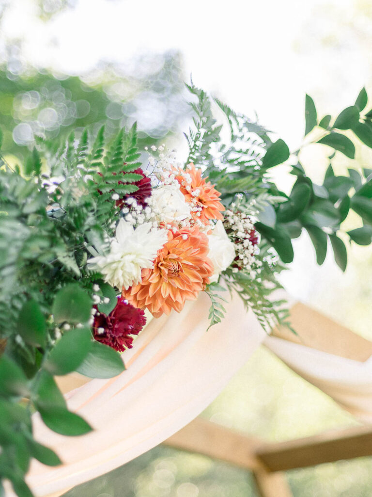 coral and orange wedding arch floral decor with greenery