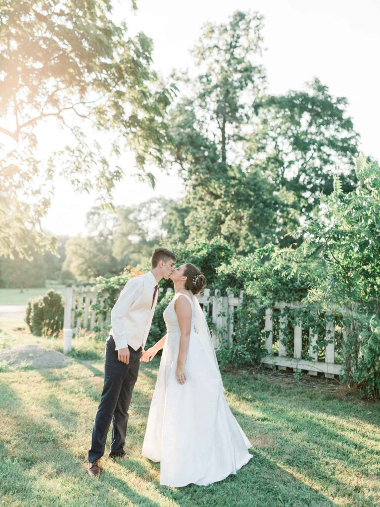 groom kissing bride during sunset gold hour by Chinling Photography