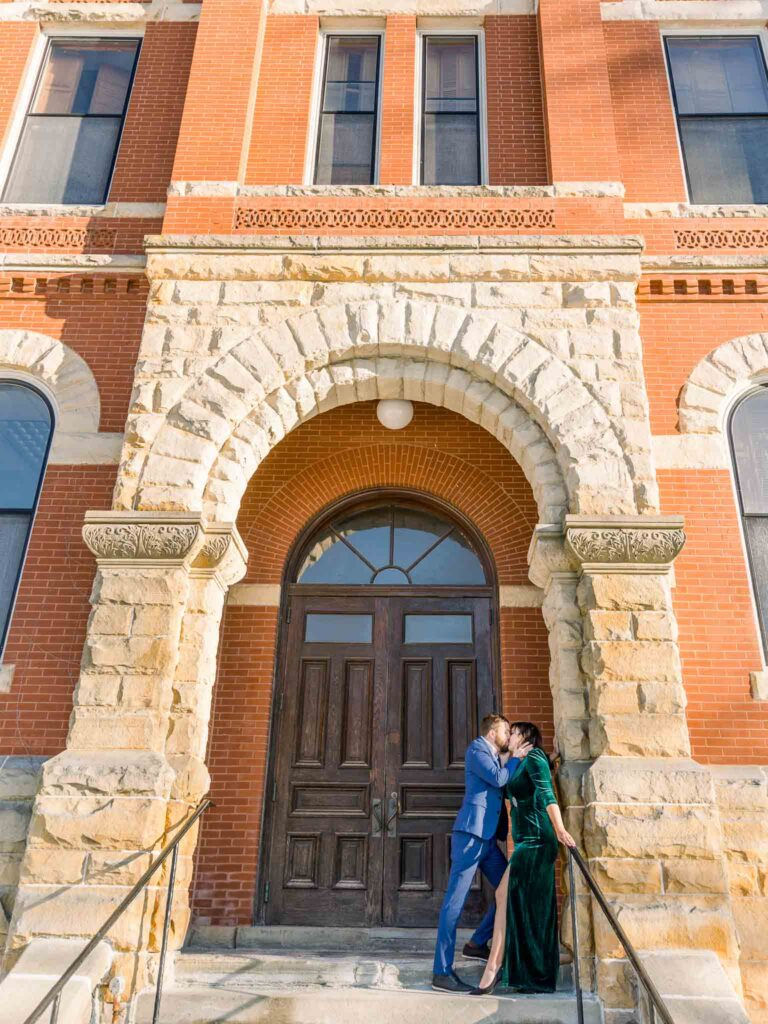 engagement session couple posing in front of Livingston County Courthouse entrance