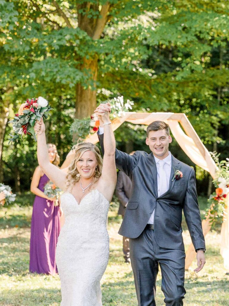 bride and groom with their hands up under wedding arch