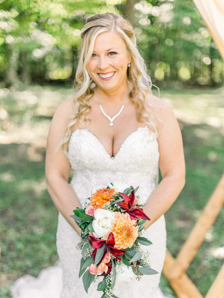 bride holding peach and blush bouquet